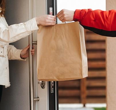 repartidor entregando bolsa de carton