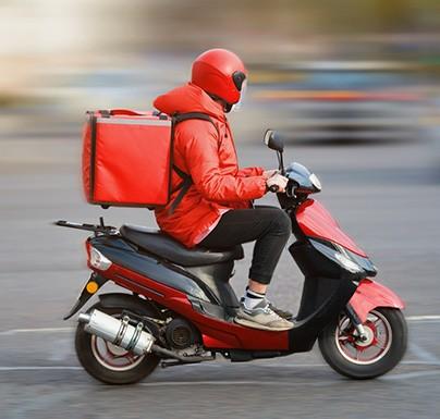 persona en moto con casco y abrigo rojo