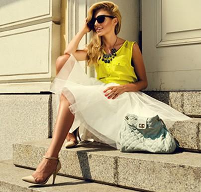 mujer rubia posando con gafas y vestido en una escalera