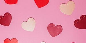 corazones rojos y rosas con fondo rosa